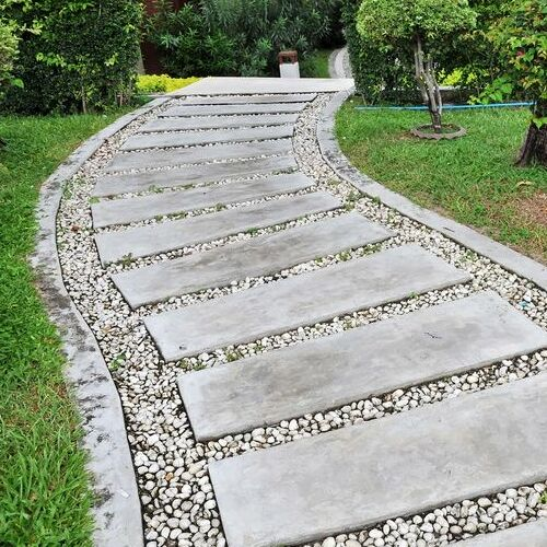 A Stone Garden Walkway With Concrete Curbing.
