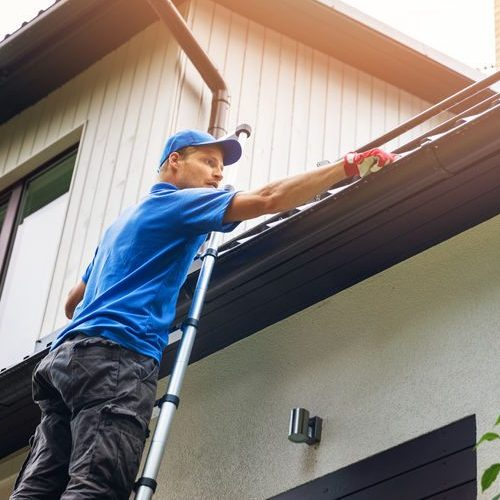 A Picture of a Man On a Ladder Cleaning Gutters.