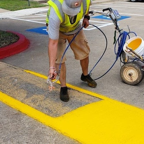 A Picture of a Man Adding Paint To Speed Bump.