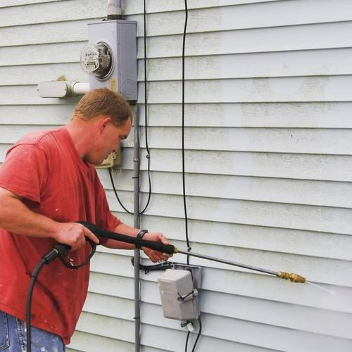 A Picture of a Man Using Pressure Washer To Remove Mold From Vinyl Siding.