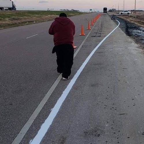 A Picture of a Man Painting the Road.