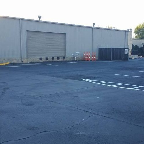 A Picture of a Parking Lot of a Warehouse.