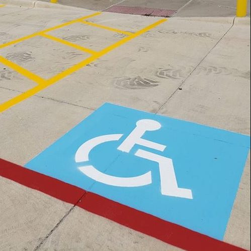 A Picture of a Parking Lot with a Handicap Logo.