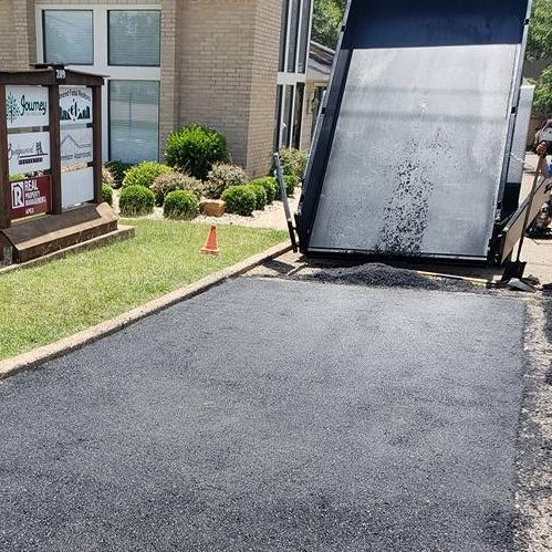 A Picture of Asphalt Being Applied On a Driveway.