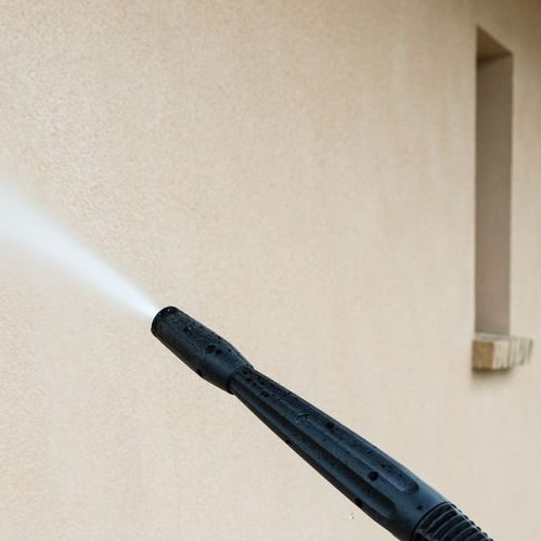 A Picture of Power Washing the Wall of a House.