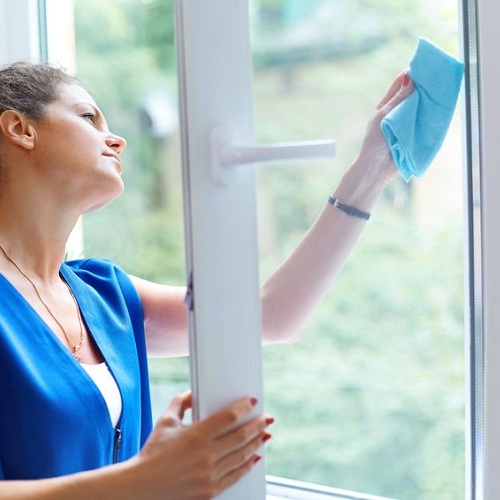 A Woman Window Washing at Home