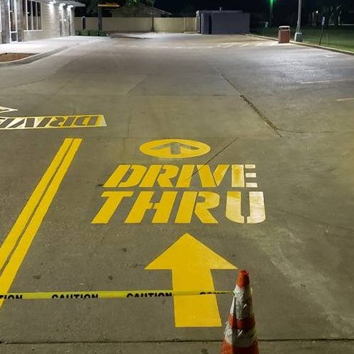 A Picture of Yellow Paint On Ground That Says Drive Thru.